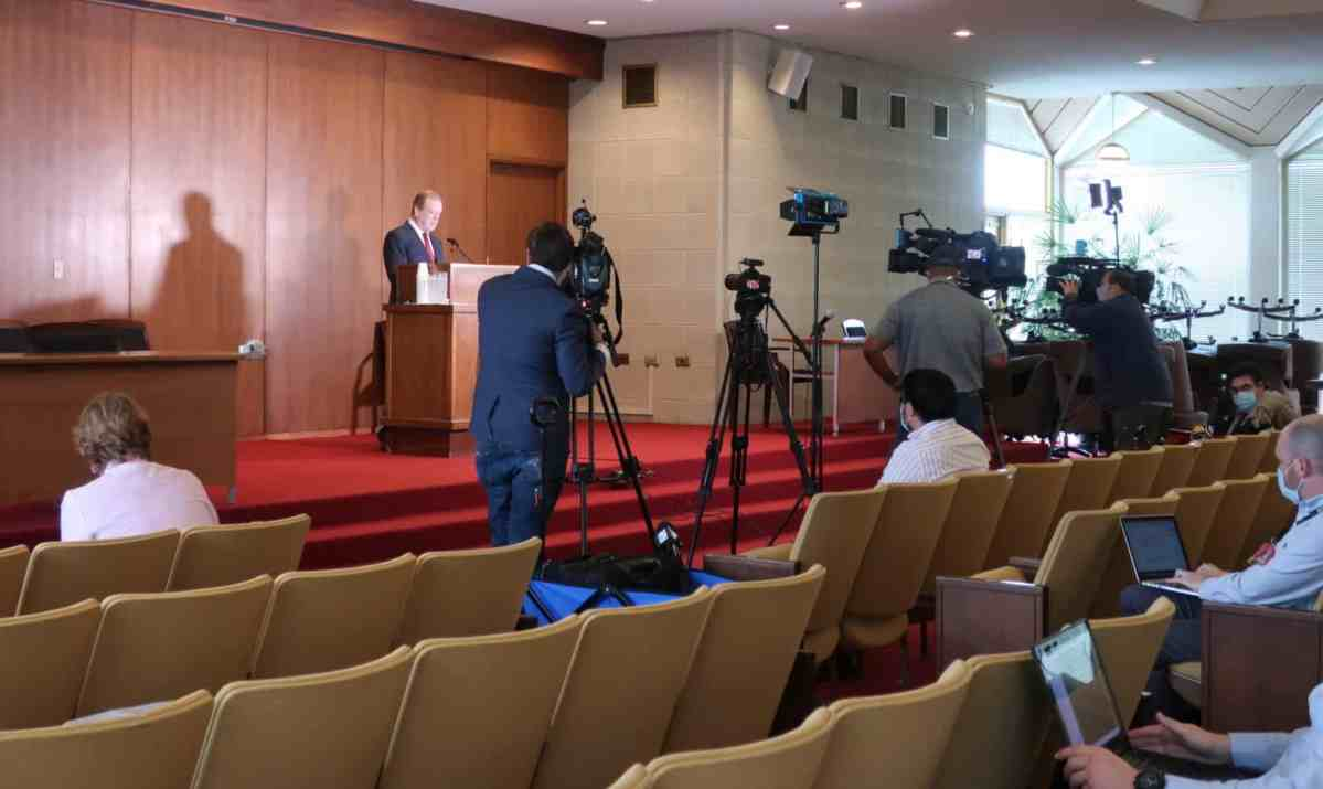 shows a man standing in the front of a room at a podium, there are cameras and mostly empty seats in front of him, the result of social distancing to prevent transmission of COVID