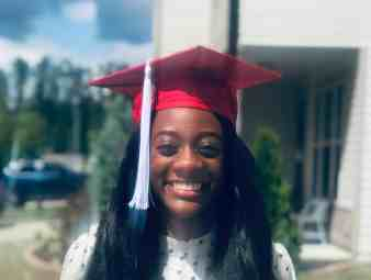 North Carolina State psychology graduate Kyria Mabiala smiles in her graduation cap. But her ceremony has been delayed by COVID