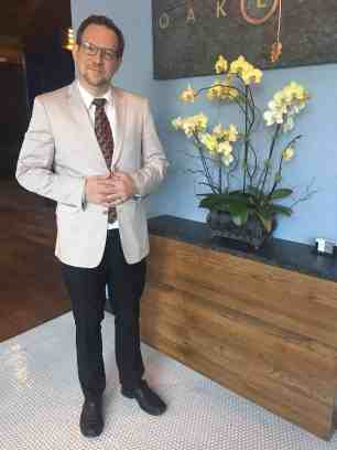 shows a man in a suit jacket standing next to a vase of flowers