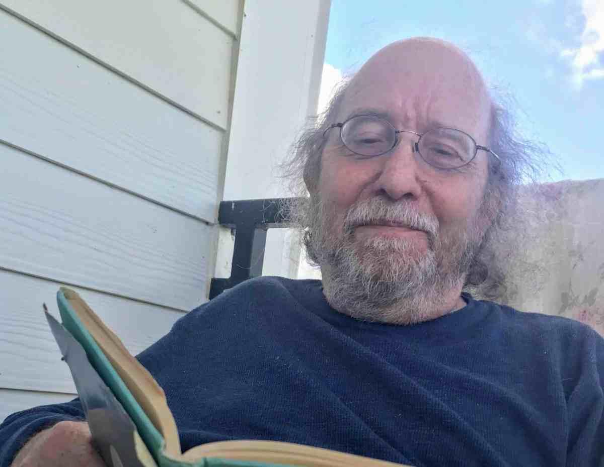 man sits reading worn book