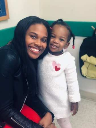 shows a beautiful african american woman with an adorable little african american girl who has all her vaccinations. They are hugging.