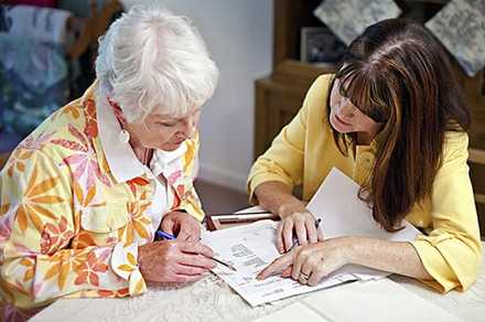 shows a younger woman with an older woman at a table, they're working on papers together. It could b esomething about COVID.