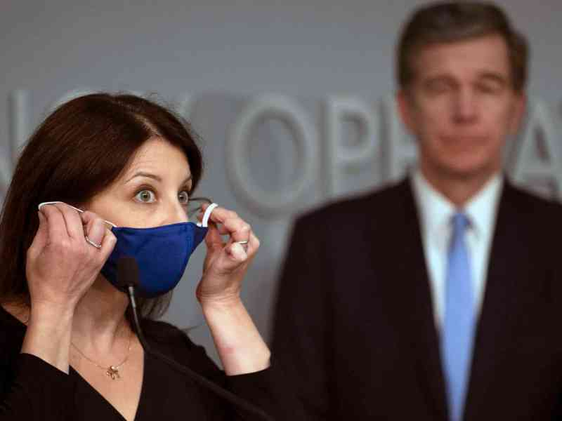 shows a woman who is demonstrating how to wear a mask for COVID prevention. A man behind her looks on.