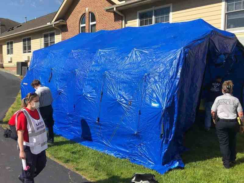 Members of the Henderson County Rescue Squad enter the decontamination tent outside Cherry Springs Village, an assisted living facility. The squad assist staff remove PPE.