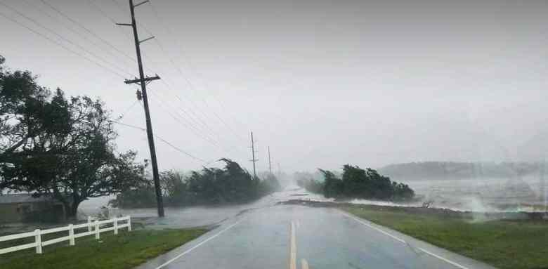 Wind blows trees and water across a flooded road during the storm. Many believe climate change contributed to the ferocity of this and other recent storms.