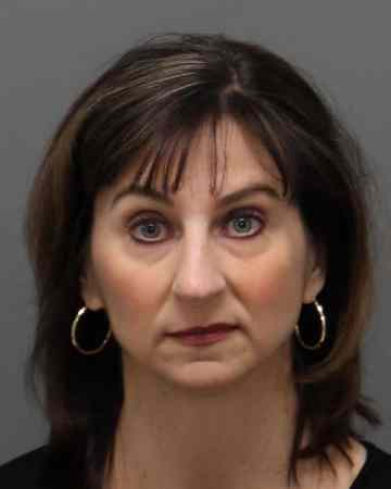 Mugshot of a brunette woman, Laura Riddick, after she was arrested for embezzlement.