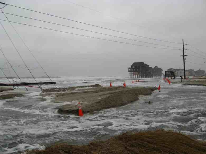 shows a road that's wiped out by a roiling sea.Houses on stilts that are now in the surf are visible in the distance. Many believe climate change contributed to the ferocity of this and other recent storms.