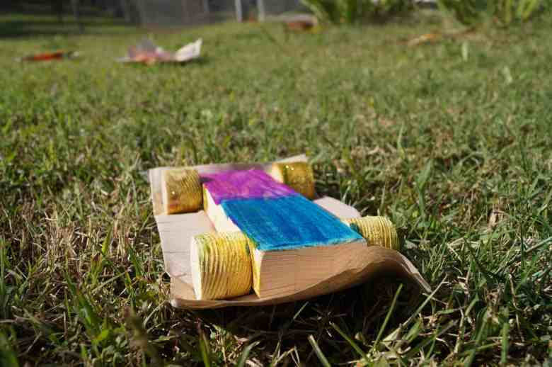 We see a toy car made out of a rectangular plank of wood, roughly painted across the top in two neat blocks of color -- one amethyst, one deep cerulean blue. The wheels are painted gold, which glistens in the sun as the car dries in the grass outside. The cars were made as a craft at the October 2019 Parent Day at Orange County Correctional Center.