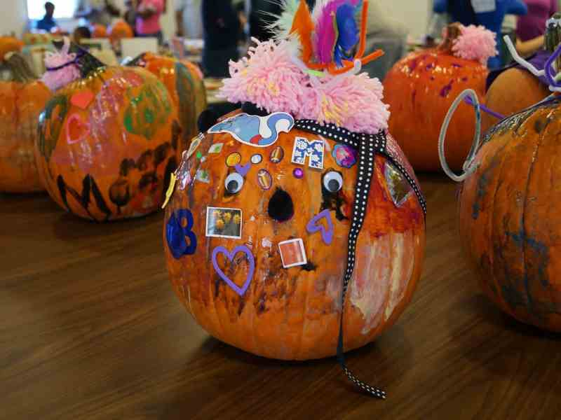 We see several pumpkins with decorated with googley eyes, stickers and multicolored acrylic paint. In the center, the heart-laden face of an orange pumpkin wearing a pink yarn hat with feathers and rainbow pipecleaners looks back at us. The pumpkins were made at the October 2019 Parent Day at Orange County Correctional Center.