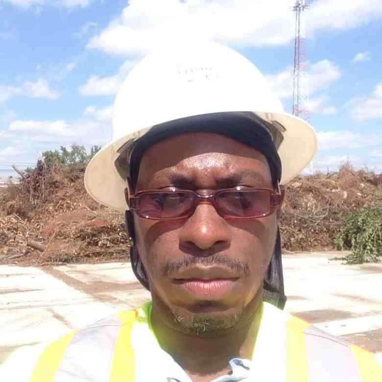 close up of a Black man in reflective gear, a hardhat and sunglasses