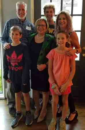 a family of five - two boys and one young girl - pose with Charlotte mayor Vi Lyles