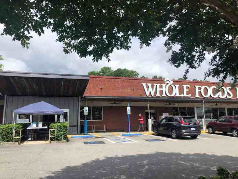 We see a tent outside a Durham Whole Foods, where an employee waits to screen patrons and ensure they're wearing a mask.