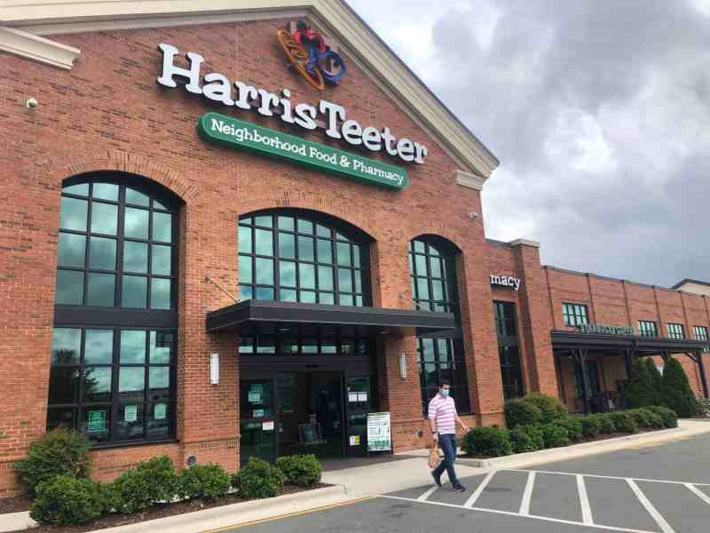 We see a masked person exiting a Durham Harris Teeter on an overcast day. Behind him, a sign tells customers to wear a mask.
