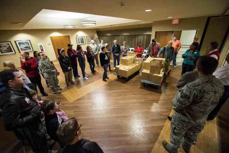 shows a group of people, many of them dressed in military uniforms, gathered around a pallet of boxes in the hallway of a building.