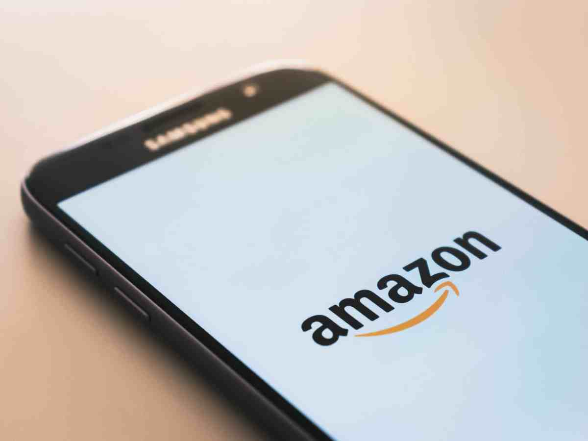 photo shows a black Samsung phone with a white screen showing just the word Amazon and the company's logo.