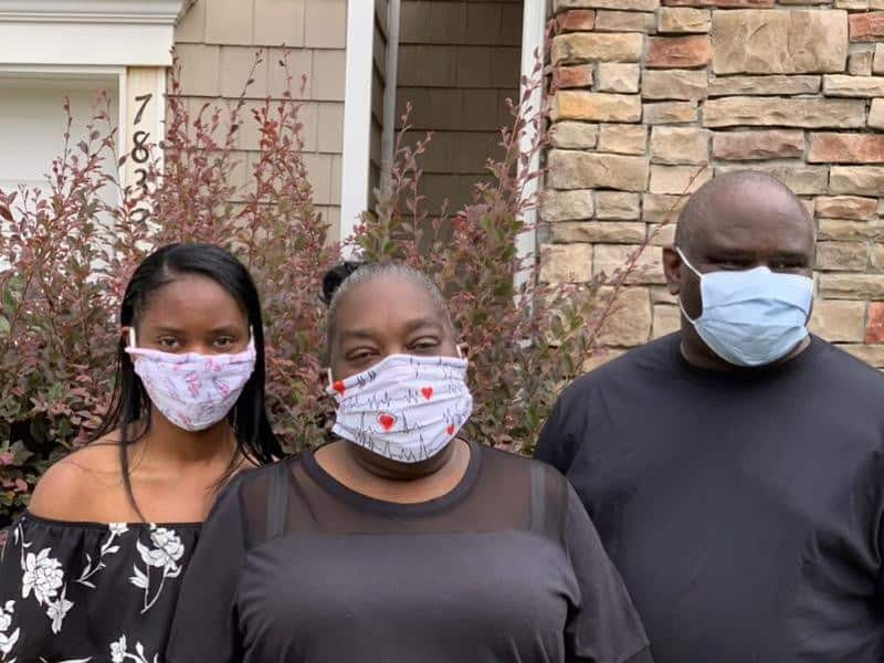 image shows a family of three, all dressed in black and wearing red and white masks