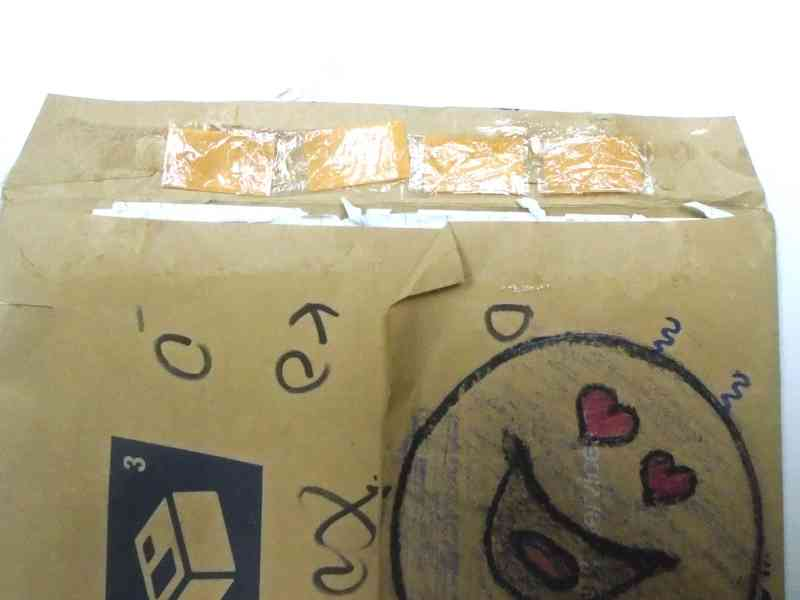 shows a large envelope with drawings on it, inside the flap are taped four strips of Suboxone wrapped in plastic wrap.