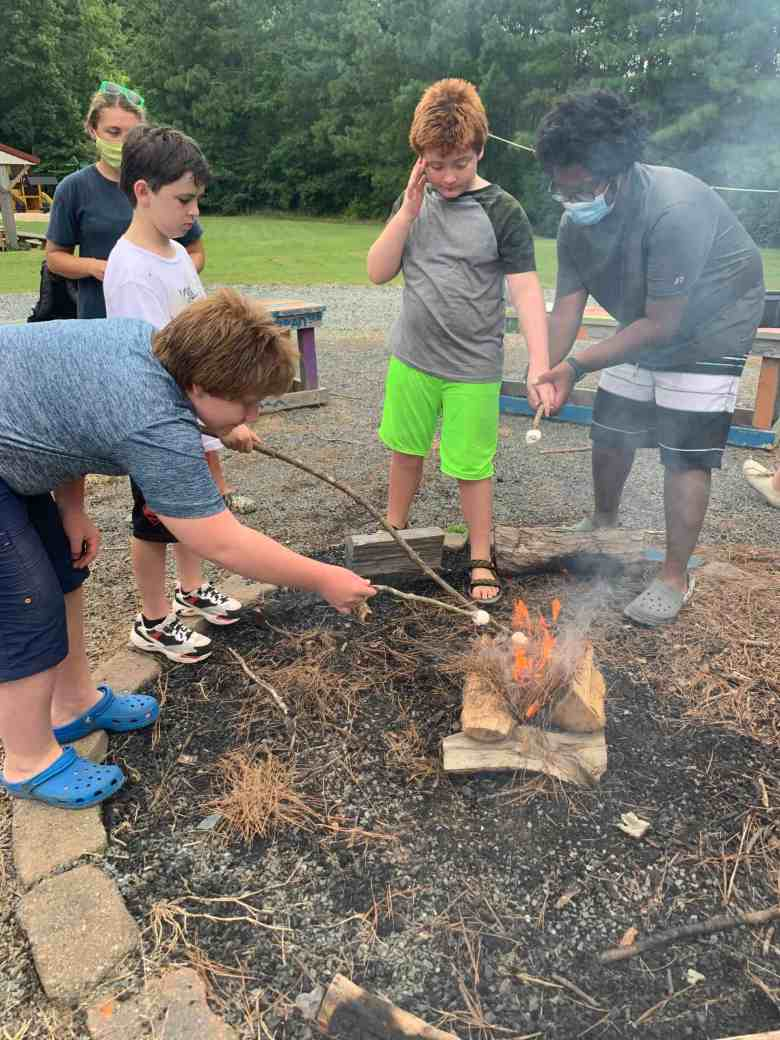 young people use sticks to roast marshmallows over an open campfire. Some wear masks to preven the spread of COVID.