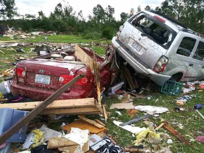 shows a glowering sky with trees in the distance. Closer to the camera, there is debris and two cars piled on top of one another, heavily damaged