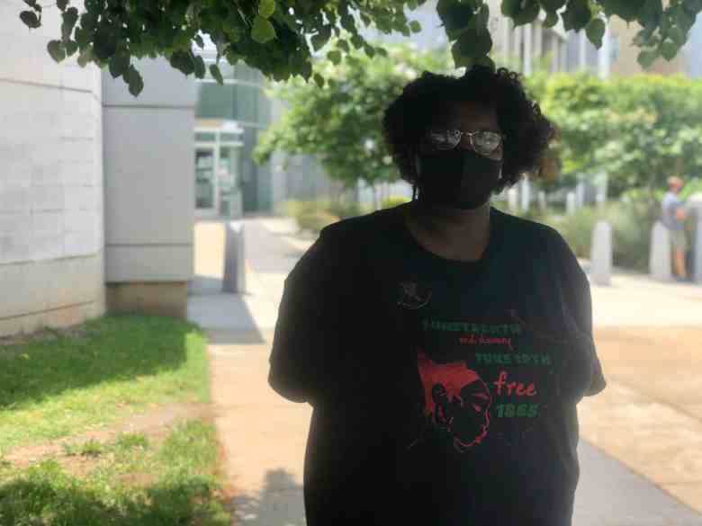 """We see Andréa """"Muffin"""" Hudson, director of the North Carolina Community Bail Fund of Durham, wearing sunglasses and a mask as she waits to bail out black fathers outside the Durham County Detention Facility. Her organization raised $100,000 for bail funds on Father's Day 2020."""