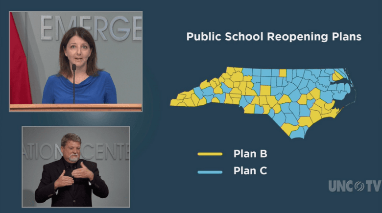 shows a woman in one box on the television screen, a sign language interpreter in another box and a map displaying a mix of yellow and blue counties to represent how schools are approaching reopening this fall.