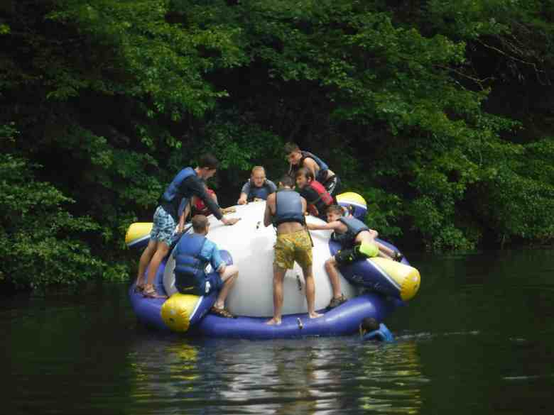 shows a group of young people hanging onto a large inflatable toy in a river.