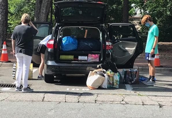 Woman and college student pack bags into an SUV