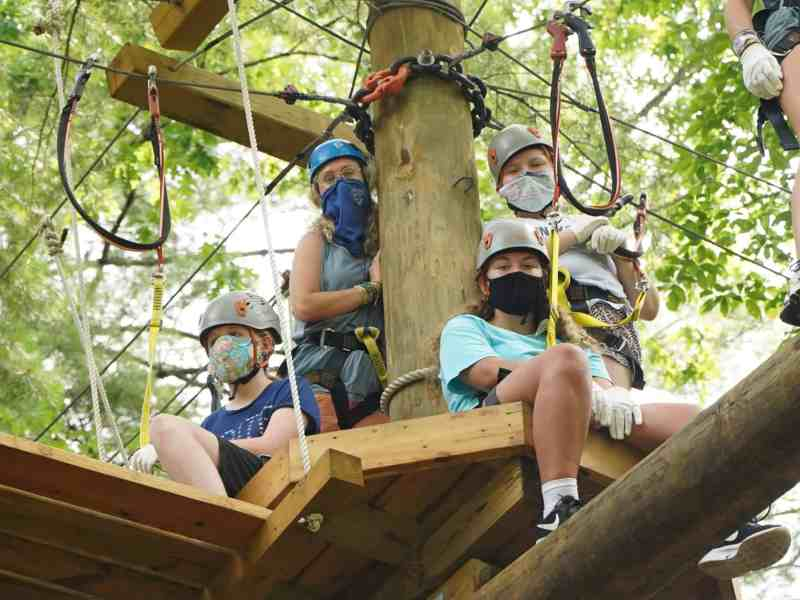 shows a group of girls on a zipline platform, all wearing safety gear and face coverings