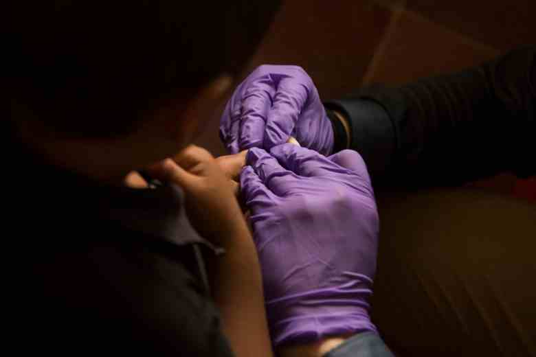 We see the back of a child's head and adult hands in purple gloves administering a finger prick blood test