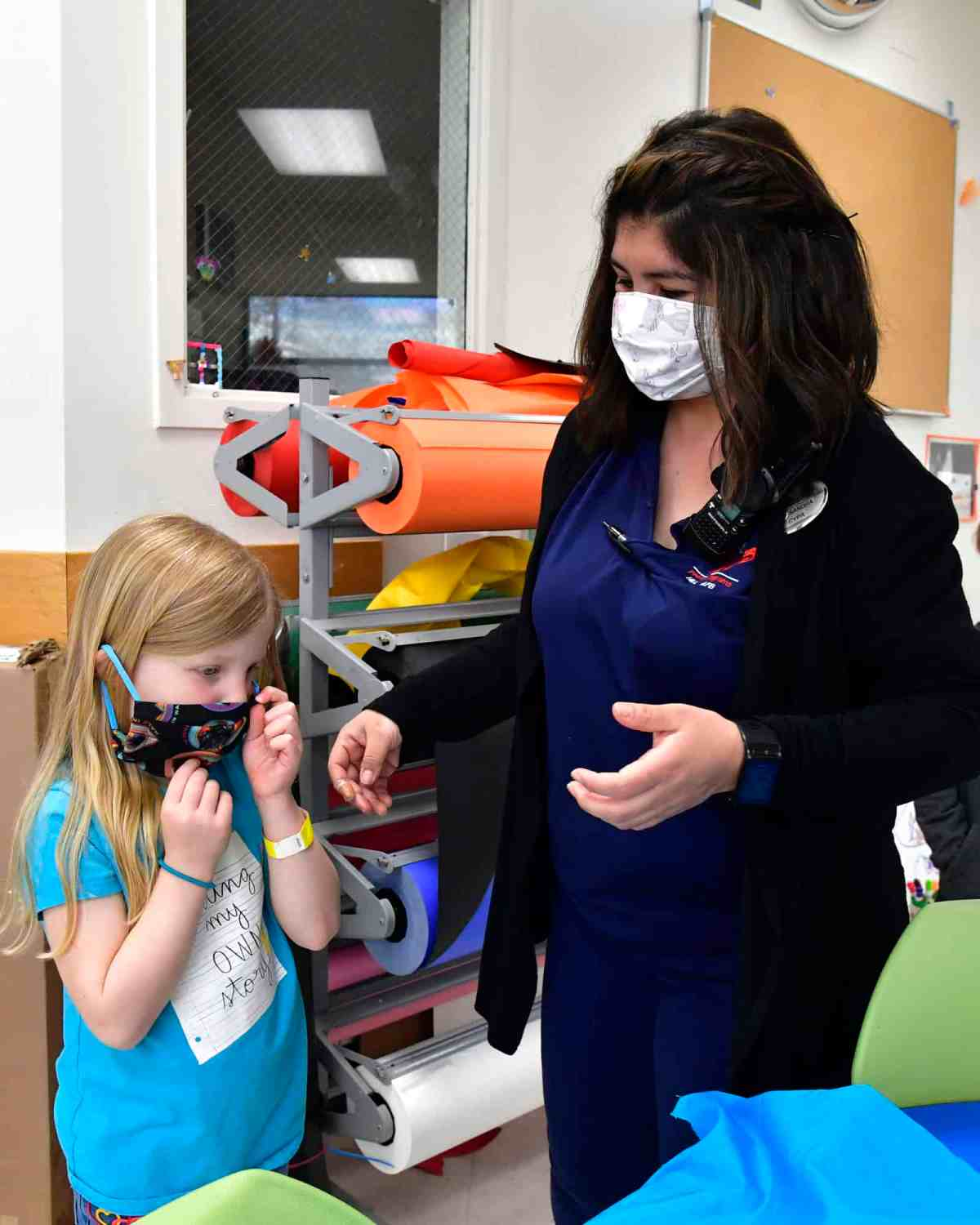 a small blonde girl in a t-shirt puts on a mask while a dark-haired woman stands by ready to help