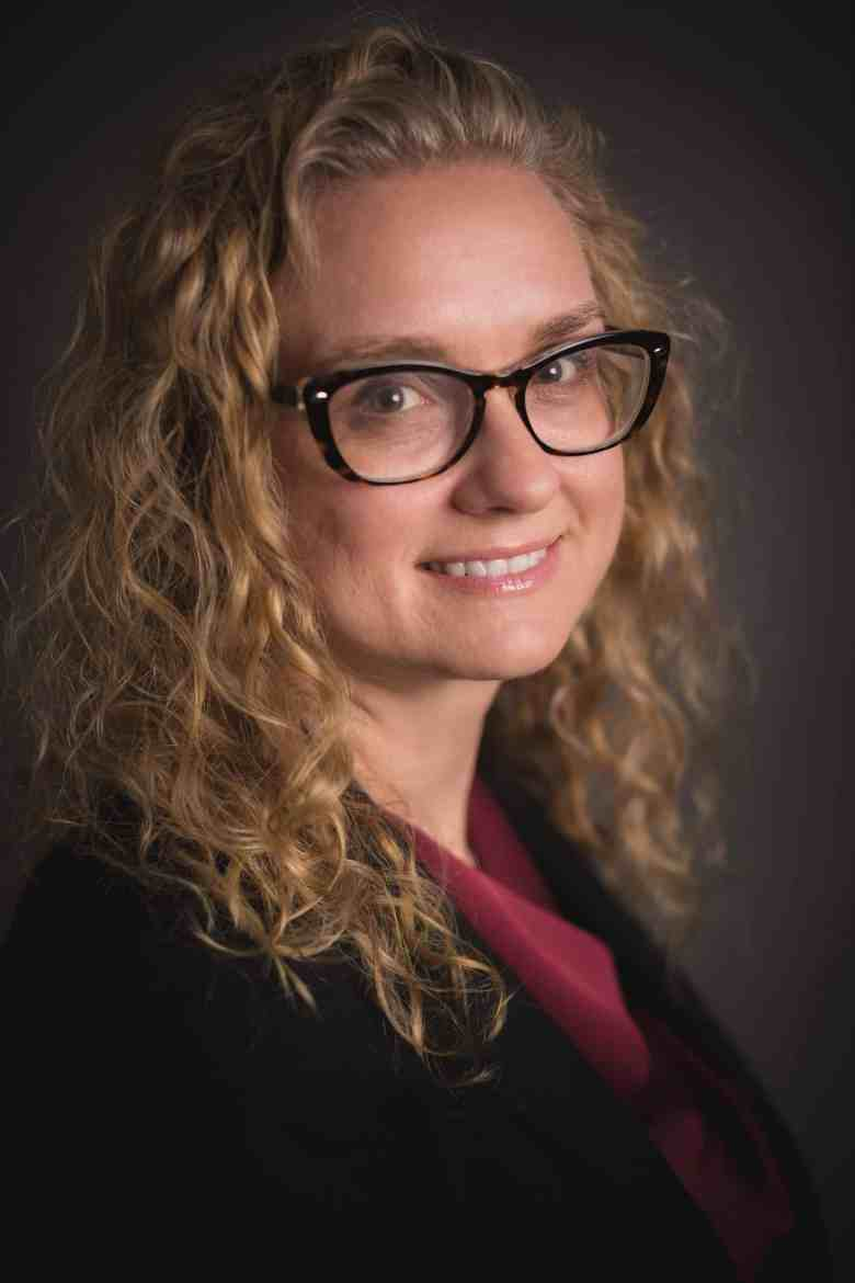 photo shows a blonde woman with curly hair, glasses, a red shirt and a black blazer smiling at the camera