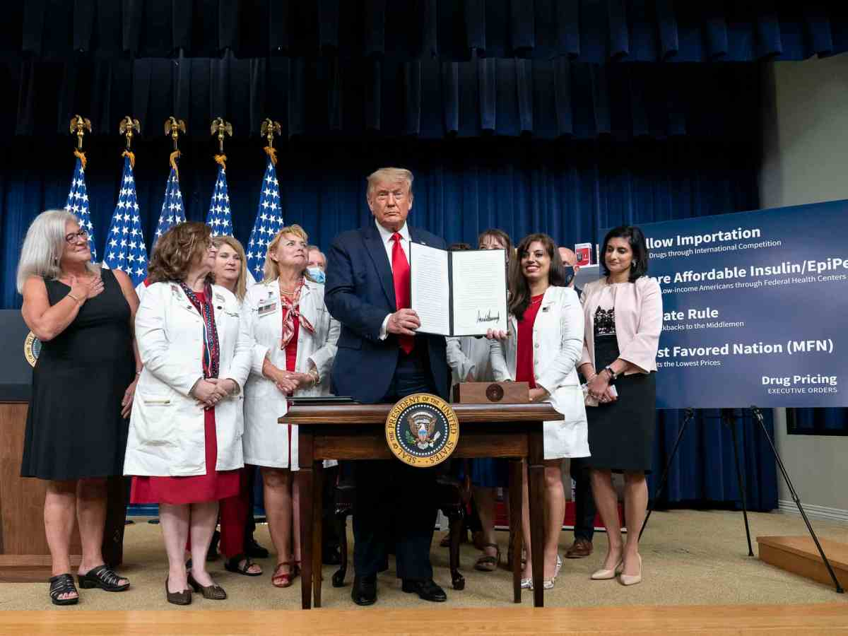shows Pres. Trump holding up his executive order, a group of women in white lab coats are behind him, an easel on his left lists the purposes of the four executive orders he talked about that day