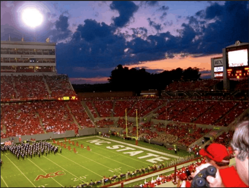 shows a view down onto the field at Carter-Finley Stadium band members on the field, with sunset clouds beyond. In the foreground, are several people, one is holding binoculars
