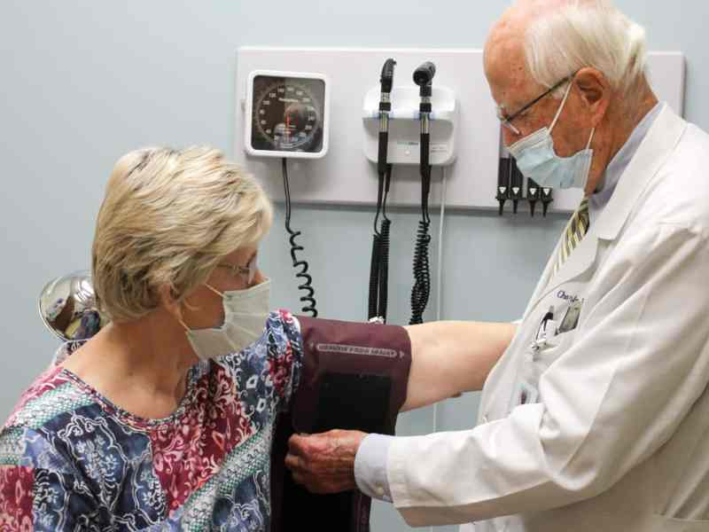 A physician in a white coat is putting a blood pressure cuff on a patient's arm.