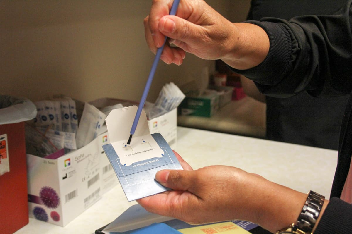 A woman holds a tiny card with a brush, demonstrating a colorectal cancer screening that can be done at home.
