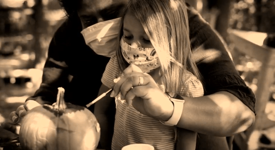 Sepia tone image of a young girl with an older man both wearing a mask against COVID, they're painting a pumpkin