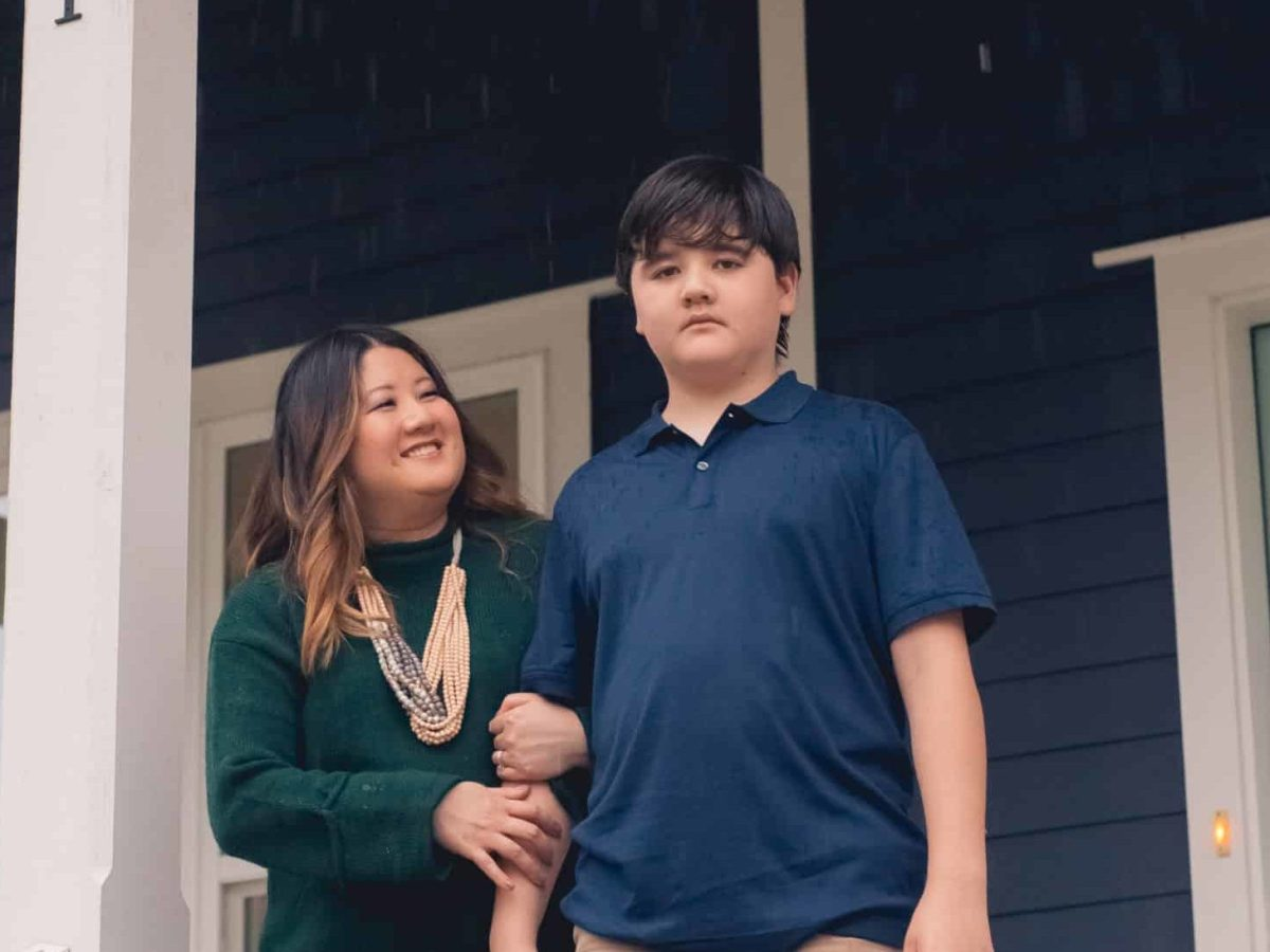 mom and son standing on front porch