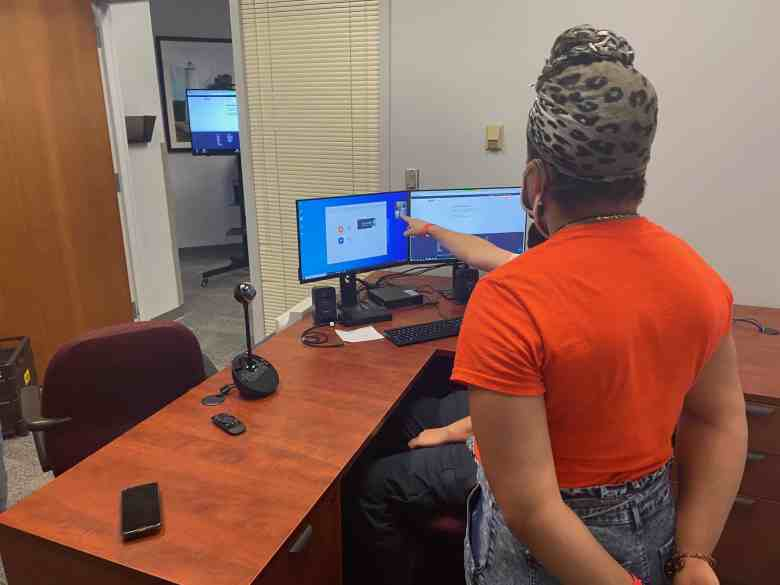 We see Zion Lemelle, a Black woman in an orange You Can Vote shirt, being trained on how to operate Mecklenburg County Detention Center's computers ahead of a virtual voter registration drive.