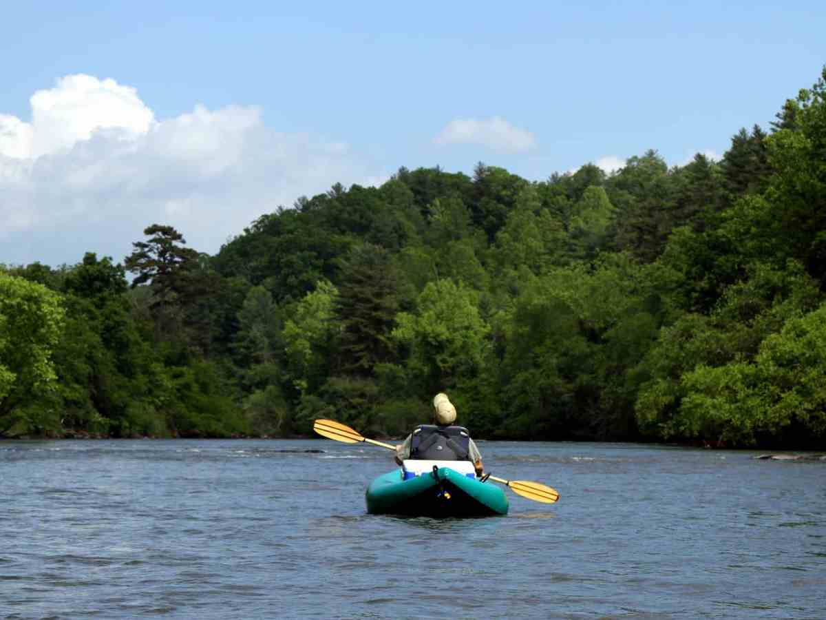we see a man kayaking away from the photographer down the French Broad River toward a wall of trees and wide blue skies