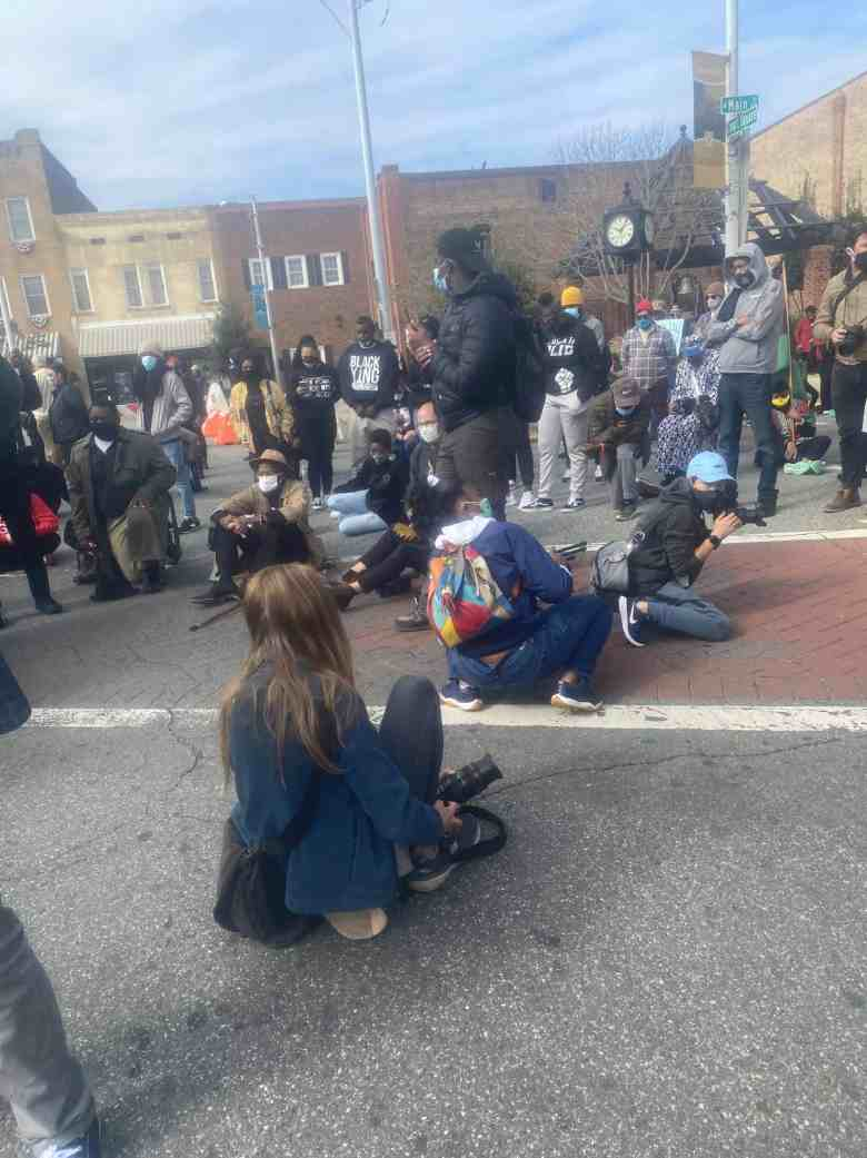 We see marchers, including children, sitting during a moment of silence for George Floyd during a voting rights rally in Graham, North Carolina, on Oct. 31. Law enforcement released pepper spray on the crowd shortly therafter.