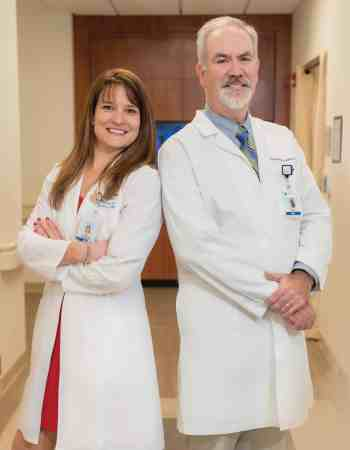 Two doctors in white coats stand in a hallway of a center where they address cancer risk with lifestyle change