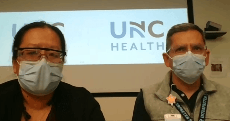 Shows two people, both wearing masks and goggles to prevent COVID-19 transmission, sitting in front of a sign reading: UNC Health. They've both received the COVID vaccine.