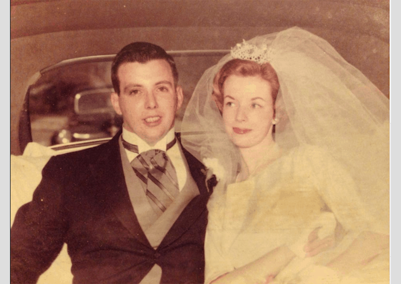 shows a yellowed image of a newlywed couple in vintage bridal attire in the back of a car