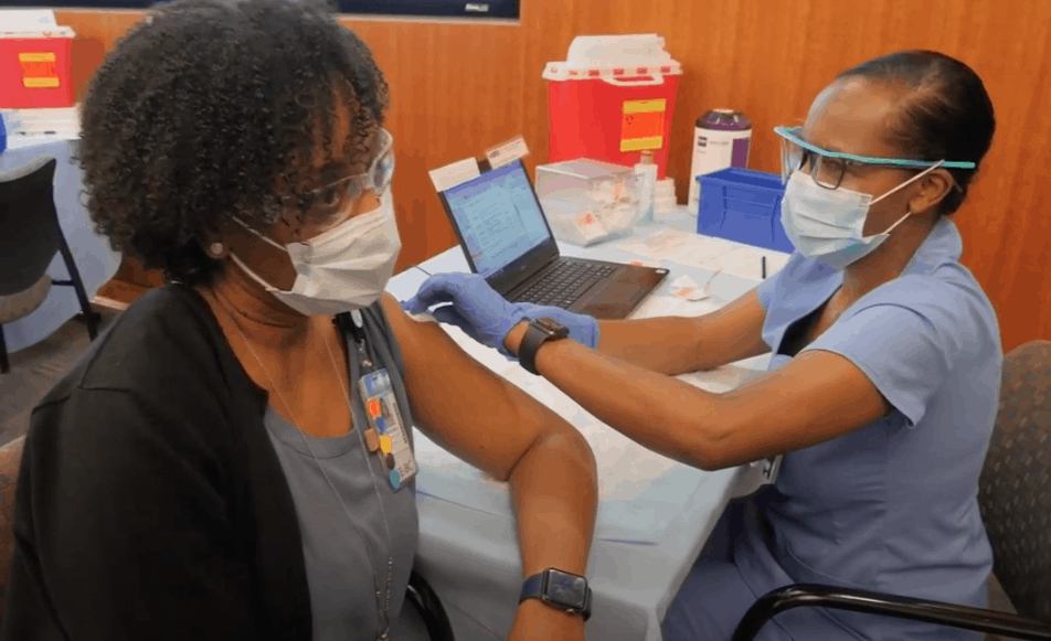 shows an african american woman who has just gotten an injection against COVID-19 from another woman, They're both wearing masks and goggles.