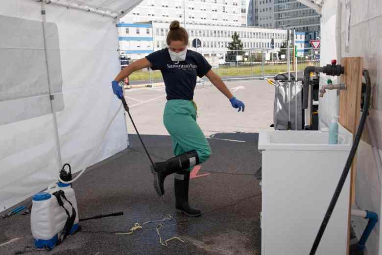 Woman is spraying her rubber boots to reduce the spread of coronavirus in front of a hospital building. There are medical tents in the background
