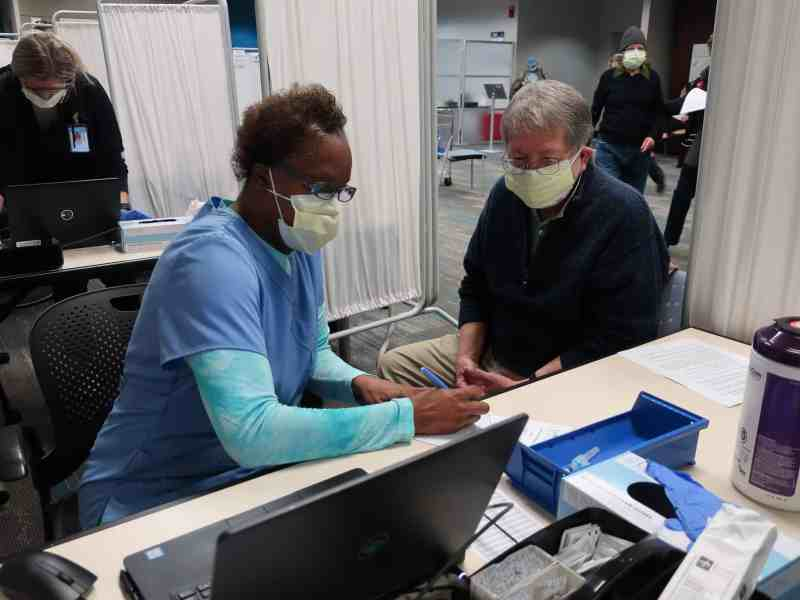 shows a woman at a table with a laptop and implements to give a vaccine talking to a man. The're both wearing masks to prevent COVID.