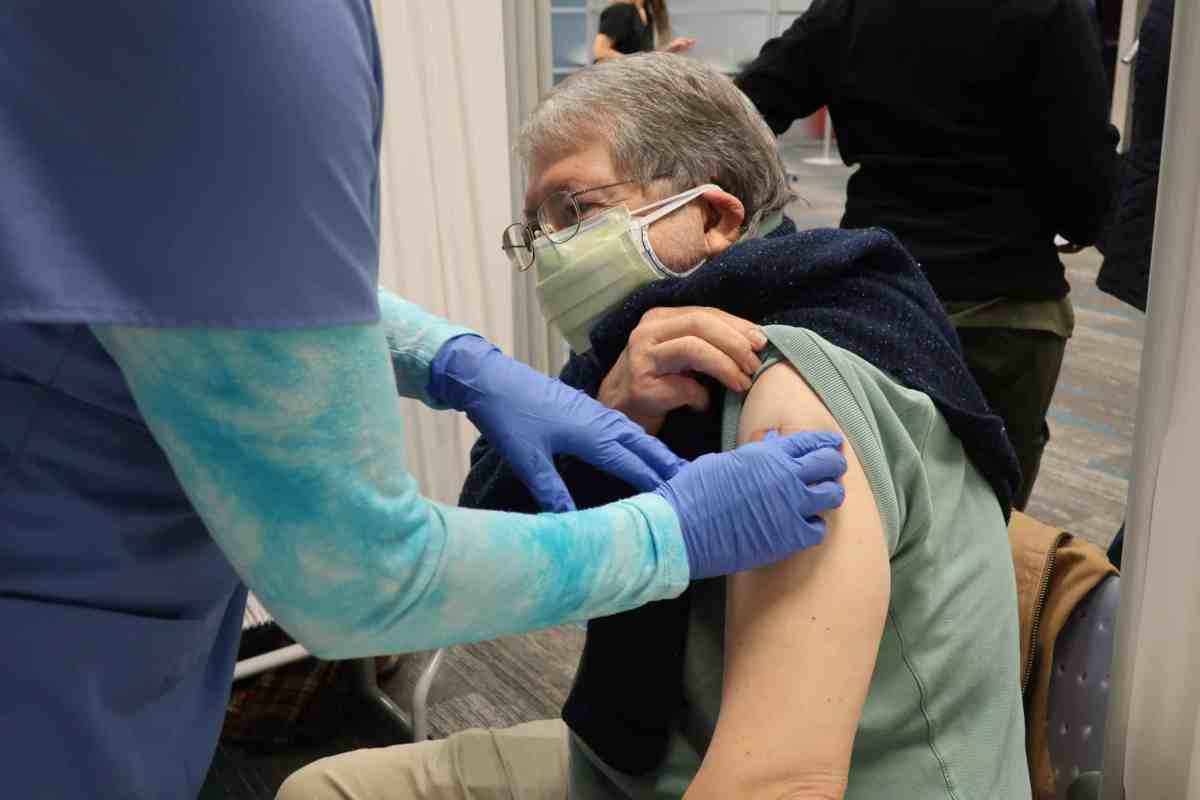 Shows an elderly gentleman with a face mask on and sleeve rolled up receiving a COVID vaccine from a nurse with purple gloves.