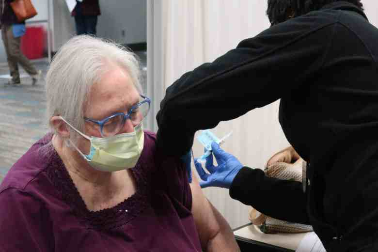 an elderly woman with gray hair sits while receiving a COVID vaccine shot in her left arm