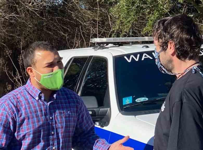 two men wearing masks talking next to an EMS vehicle