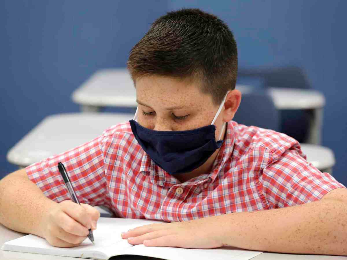 shows a freckle faced boy in a mask to prevent coronavirus transmission sitting at a school desk with a notebook and pen.